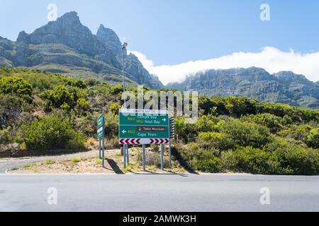 Panneau vert sur M62 route principale, Camps Bay Drive,montrant les directions à Hout Bay et Cape Town avec Table Mountain téléphérique et gare supérieure derrière Banque D'Images