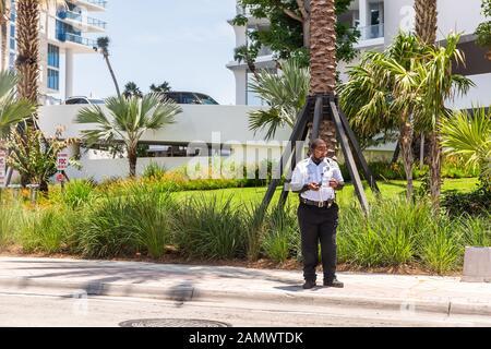 Sunny Isles Beach, États-Unis - le 8 mai 2018 : policier de garde de sécurité homme dans la ville de North Miami, en Floride, sur l'A1A Collins Avenue Road Street Banque D'Images