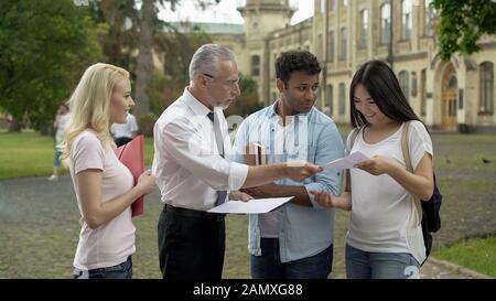 Professeur adulte retournant des tests avec des marques à des étudiants multiethniques, de bons résultats Banque D'Images