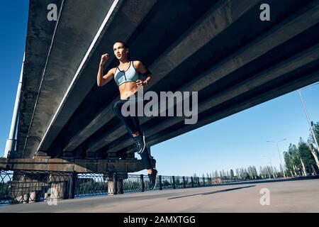 Femme sportive tournant à l'extérieur sous le pont de la ville. Belle femme dans les vêtements de sport. Le mouvement dynamique Banque D'Images