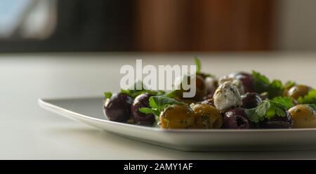 Salade grecque frais basé sur olives vertes et noires avec des morceaux de fromage blanc et de persil, une cuisine méditerranéenne traditionnelle