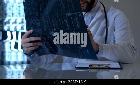 Spécialiste des lésions de la moelle épinière examinant les rayons X des patients au bureau, la vertèbre Banque D'Images