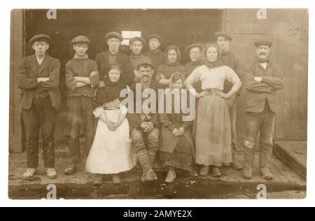 Edwardian photographie de groupe de jeunes filles et garçons avec des hommes plus âgés, peut-être les surveillants,vêtu de vêtements de travail - buses, de châles. Ce sont probablement les travailleurs de l'usine comme une fille a une ceinture avec des ciseaux en eux comme chez les autres travailleurs de l'usine photos éventuellement le Lancashire, Angleterre, Royaume-Uni, vers 1910 Banque D'Images