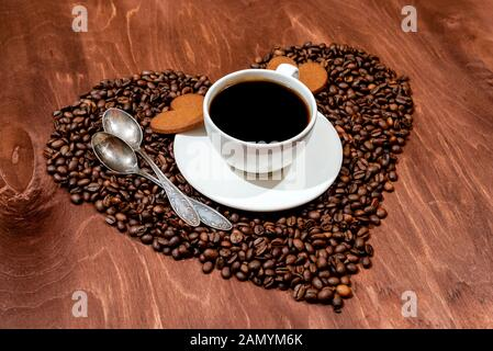 Tasse à café blanc, d'épices en forme de coeur et deux cuillères sur une base en forme de coeur fait avec des grains de café - image Banque D'Images