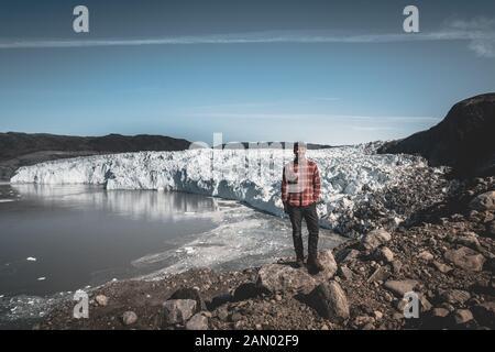 Un jeune homme traveler'debout devant Eqip Sermia appelé glacier Eqi Glacier. Mur de glace en arrière-plan. La notion de réchauffement global et