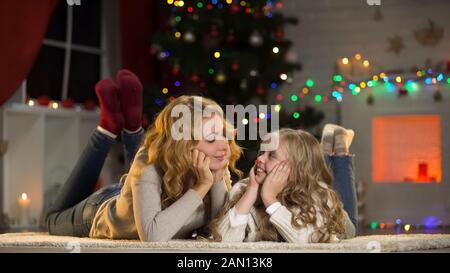 Jeune mère et fille posée sous l'arbre de Noël, regardant l'un l'autre Banque D'Images