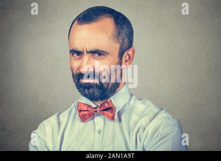 Gros plan portrait de jeune homme en colère et grincheux, isolé sur fond de mur gris. Émotions humaines négatives sentiment d'expression faciale Banque D'Images