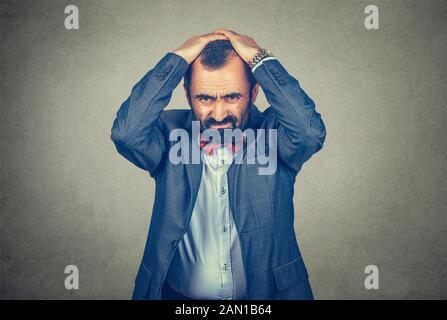 homme d'affaires tenant les mains sur la tête dans la frustration, a souligné l'homme contrarié frustré isolé sur fond de mur gris. Émotions humaines négatives Banque D'Images