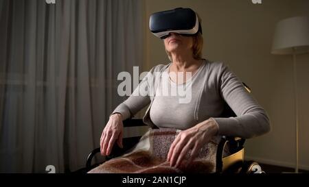 Dame mûre en fauteuil roulant portant un casque vr pour voir le mot technologique magique Banque D'Images