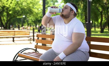 Obscurcissement du jeune homme assis sur un banc et de l'eau potable après une séance d'entraînement en plein air Banque D'Images