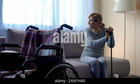 Une dame pour personnes à mobilité réduite s'assoir sur un canapé et regardant dans la fenêtre, un fauteuil roulant vide dans la chambre Banque D'Images