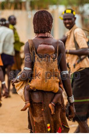 Femme Hamer portant bébé sur son dos, marché hebdomadaire de la tribu Hamer à Turmi, Omo Valley, Ethiopie. Banque D'Images