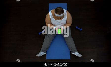 L'homme grassouillet à l'aide d'application remise en forme sur smartphone, assis sur le tapis, un écran vert Banque D'Images