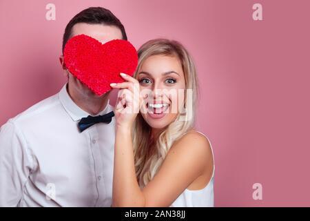 Deux amants heureux holding paper coeur sur fond rose Banque D'Images