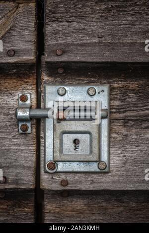 Vis coulissante fermée ancienne serrure sur une porte en bois Banque D'Images