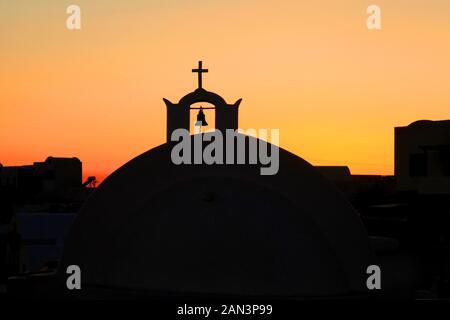 Un dôme d'église avec cloche et croix religieuse dans la ville d'Oia à Santorin, Grèce. Banque D'Images