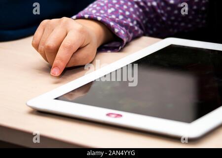 Close up Vue de face d'une petite fille à l'aide de la main et blanc tablette avec un couvercle de l'appareil photo de la vie privée, au cours de la journée