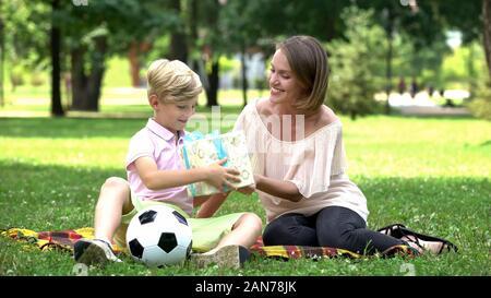 Loving mother giving present en fils sur anniversaire, incarnation du rêve de l'enfant Banque D'Images