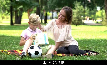 Mère attentive giving present fort de fils, un anniversaire à l'extérieur, surprise Banque D'Images