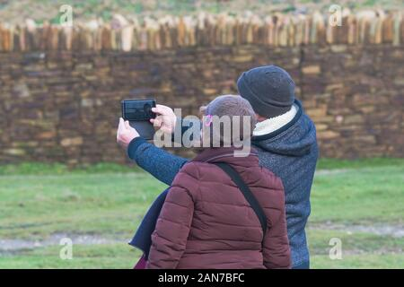 Les visiteurs qui utilisent un smartphone pour prendre une photo à selfies dans Fistral Newquay en Cornouailles.