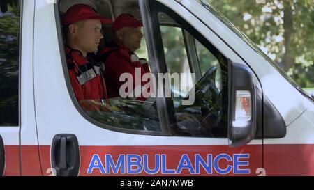 Les paramédics d'hommes assis en ambulance, prêt à chasser sur appel, les professionnels Banque D'Images
