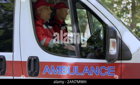Les médecins hommes assis en ambulance, prêt à chasser sur appel, les professionnels Banque D'Images