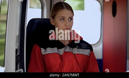 Young female paramedic assis en ambulance, prêt à chasser à l'appel, 911 Banque D'Images