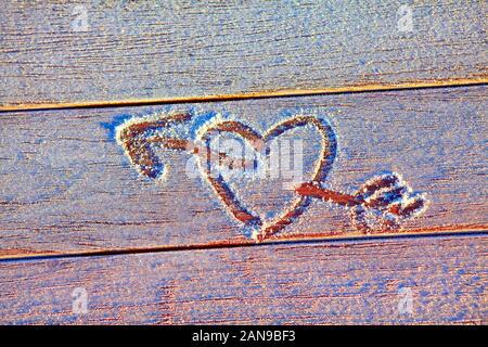 Coeur et flèche tracée sur la surface gelée Banque D'Images