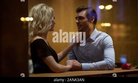 Couple sitting in restaurant et tenir la main, relation romantique, datant Banque D'Images