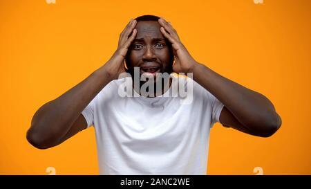 L'homme afro-américain choqué holding head, problèmes de la vie, de mauvaises nouvelles, les commères