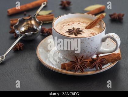Indian Masala thé chai. Boisson chaude traditionnelle indienne avec du lait et des épices sur fond de pierre sombre close up.
