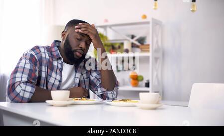 L'homme afro-américain fatigué d'avoir des maux de tête après une dure journée, se sentir épuisé Banque D'Images