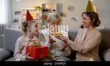 Mère et enfant de sexe féminin en chapeaux de fête gâteau donnant et d'aujourd'hui, célébrer b-day Banque D'Images