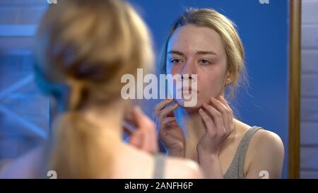 Jeune femme malheureuse à la réflexion en miroir, imperfection de la peau, de l'insécurité Banque D'Images