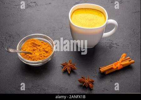 Tasse en verre de thé chai masala indien traditionnel avec des ingrédients ci-dessus. Cannelle, cardamome, l'anis sur fond texture sombre