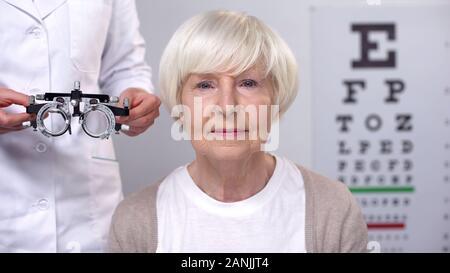 Happy senior femelle dans les lunettes à la caméra au cours de l'examen de la vision Banque D'Images