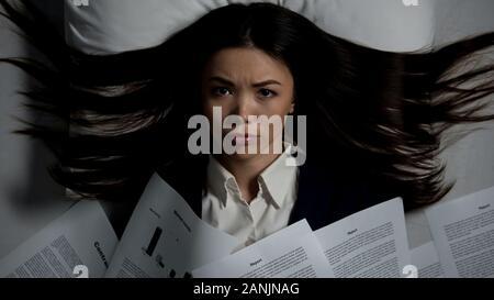 Femme a souligné couvert de documents au lit, réunion date limite, Mauvais rêve Banque D'Images