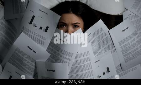 Femme couverte de pile de documents au lit, la surcharge de travail concept Banque D'Images