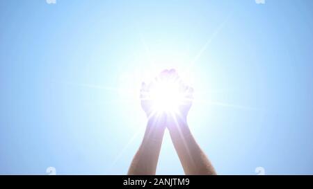Mains tenant la Lumière sacrée contre le ciel bleu, miracle religieux, rayon d'espoir Banque D'Images