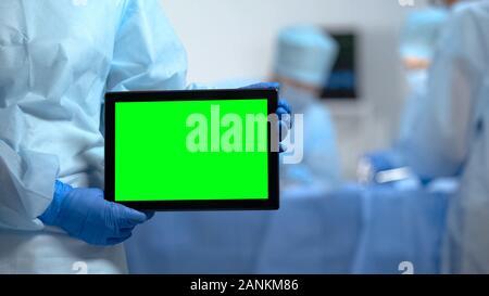 Mains de nurse holding tablet PC avec un écran vert lors de l'opération de l'hôpital Banque D'Images