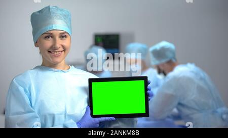 Smiling nurse holding tablet PC avec un écran vert lors de l'opération, annonce l'hôpital