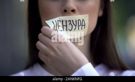 Résolument Femme, décoller la bande avec mot censuré en russe sur la bouche Banque D'Images
