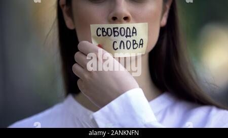Woman taking off de la bande avec la liberté d'expression expression en russe sur la bouche Banque D'Images