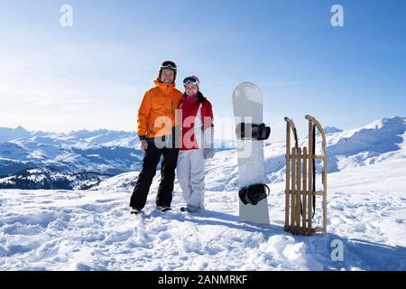 Portrait d'un jeune couple sympathique, debout près de Snow Board et traîneau en bois dans la neige Banque D'Images