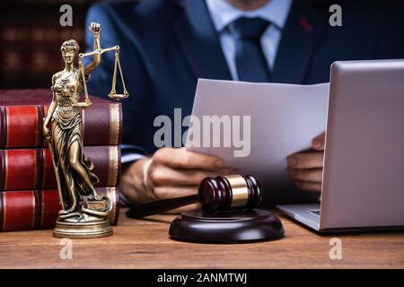 Portrait d'avocat la lecture de documents près de Mallet et ordinateur portable à 24, dans la salle d'audience