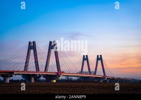 Nouveau pont moderne à double câble, lumineux et monumental, surpassant la Vistule à Cracovie, en Pologne, au coucher du soleil. Banque D'Images