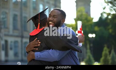 Cheerful père et fils diplômés hugging extérieur, réalisation de l'étude, de l'éducation