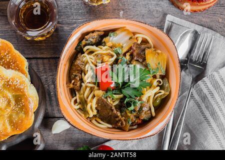 L'ouzbek et nouilles asiatiques traditionnelles lagman avec les légumes et la viande sur la table en bois rustique, d'arrière-plan. Vue d'en haut