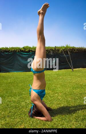 Slim woman in bikini pratiquant le yoga. Position Sirsasana Banque D'Images