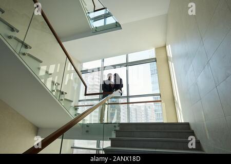 Deux jeunes collègues de soirée article par railinigs entre escaliers Banque D'Images
